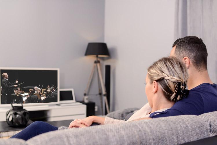 Paar schaut auf dem Sofa in den Fernseher